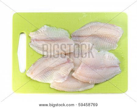Tilapia fish fillets on green kitchen board