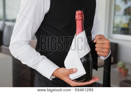 Well dressed waiter holding magnum of champagne in the patio of restaurant