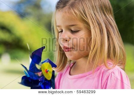 Close-up of cute girl blowing pinwheel at the park