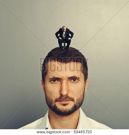 small senior man looking at big man over dark background