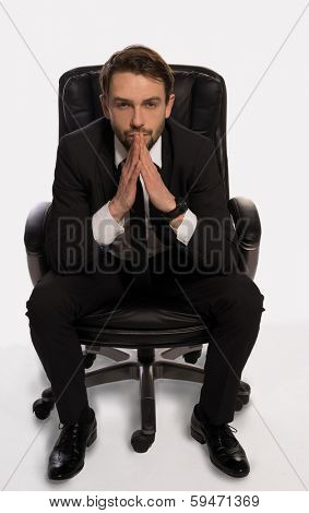Businessman with a dilemma sitting in his office chair facing the camera with his hands steepled and a seerious contemplative expression as he tires to solve a problem or reach a decision, on white