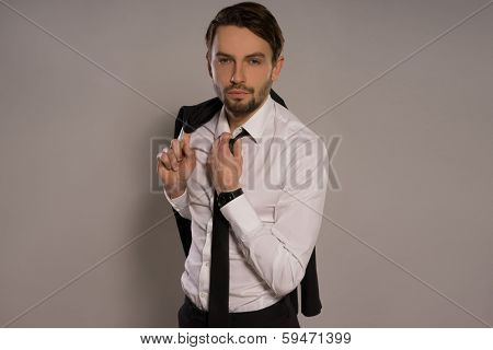 Handsome young businessman with his jacket thrown over his shoulder loosening his tie and smiling at the camera