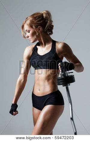 Smiling athletic woman pumping up muscules with barbell on gray background