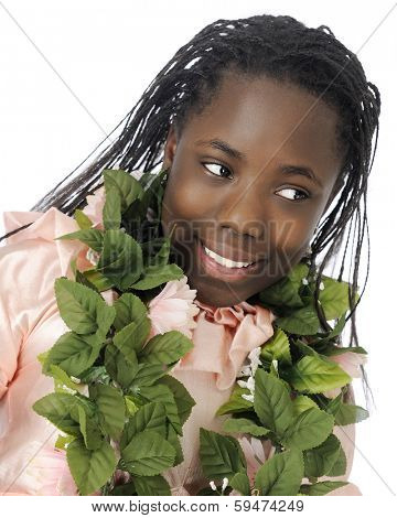 Close-up of a beautiful black tween girl with a lei of leaves around her neck.  On a white background.