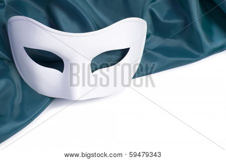 White theatrical mask and silk fabric on a white background