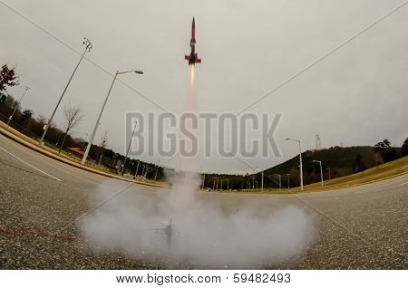 model rocket launch in parking lot on cloudy day