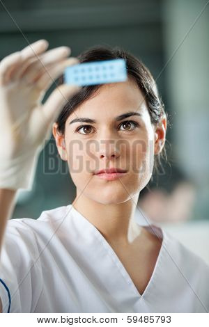 Young female scientist analyzing microscope slide in laboratory
