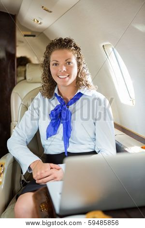 Portrait of happy airhostess with laptop sitting in private jet