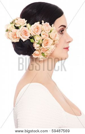 Profile portrait of young beautiful woman with roses in her hair, over white background