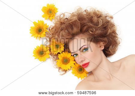 Young beautiful healthy woman with curly hair and sunflowers over white background