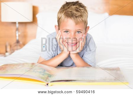Smiling blonde boy lying on bed reading a storybook at home in bedroom