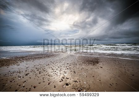 A Beach At The Seaside, With Small Stones, Stormy Sea, Dramatic Stormy Clouds And Illumination.