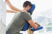 pic of physiotherapist  - Female physiotherapist giving shoulder massage to man on massage chair in hospital - JPG