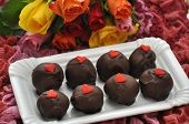 picture of red velvet cake  - Red Velvet Cake Pops with roses in the background - JPG