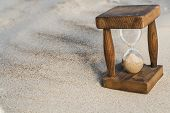 stock photo of sand timer  - Vintage hourglass in the sand with small shadow - JPG