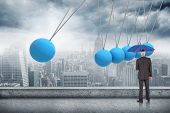 Businessman holding umbrella against newtons cradle above city