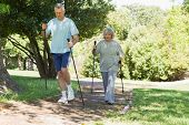 Full length of a mature couple Nordic walking on pathway in the park