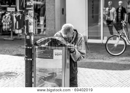 A man searching a litter bin
