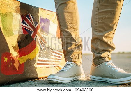 Traveler Stands Near The Suitcase With Stamps Flags
