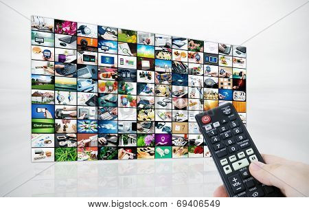 Big Lcd Panel With Television Stream Images And Remonte Control In Hand
