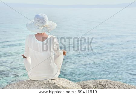 Woman with a hat facing the sea meditating