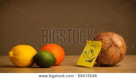 Coconut with sticky note reacting at citrus fruits