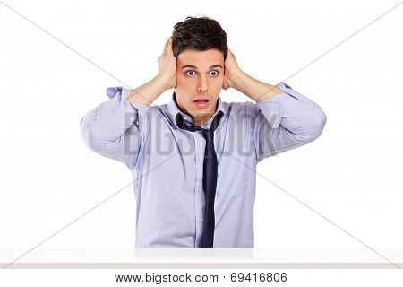 Shocked man in disbelief sitting at a table isolated on white background