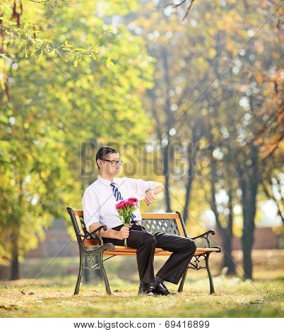 Young man holding flowers and checking the time seated on bench in park shot with tilt and shift lens