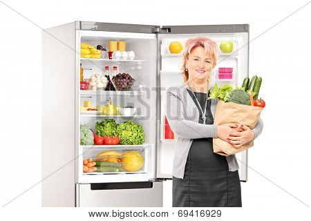 Woman with bag of vegetables in front of a fridge isolated on white background