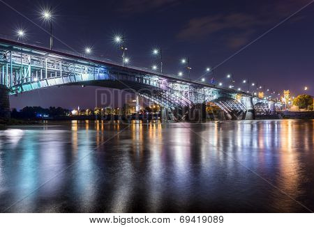Backlit Bridge At Night And Reflected In The Water.