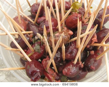 a bunch of olives with a bunch of toothpicks
