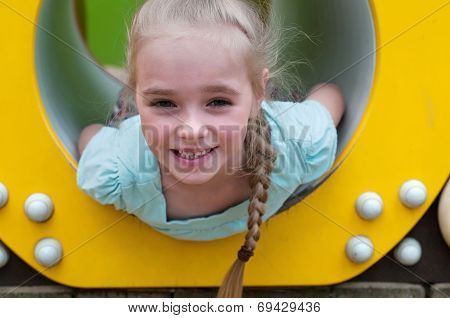 Adorable young girl sitting in crawl tube
