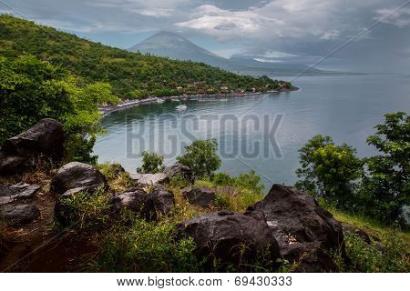 Calm lagoon with mountains on the background and wet rocks on the foreground