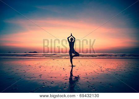 Silhouette of a woman yoga on sea coast at surreal sunset.