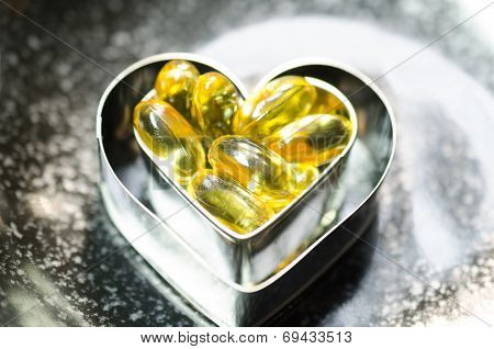 Fish Oil Capsule On Double Heart Shape Box In Smaller One  On Black Plate