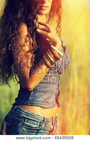young woman in jeans shorts wearing lot of braceletes on hand standing in yellow summer grass retro colors