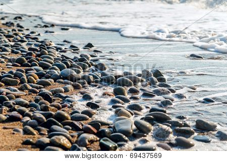 Sea Pebbles Washed By The Waves At Sunrise