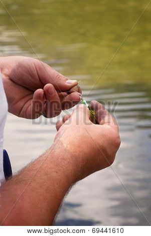 Man tying lure to fishing line