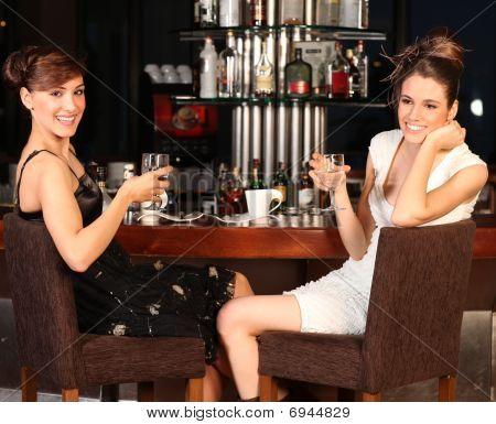 Two Beautiful Young Women Drinking Water At Bar