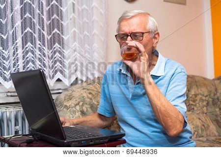 Senior With Laptop And Glass Of Whiskey