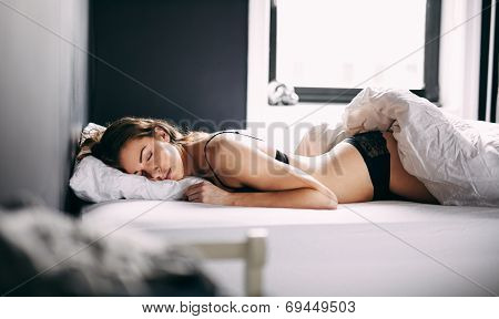 Female Model Sleeping On Her Bed