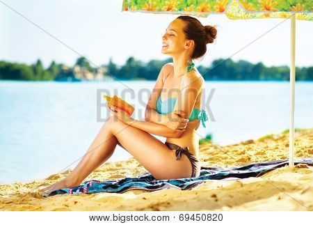 Suntan Lotion Woman Applying Sunscreen Solar Cream. Beautiful happy cute teen Girl applying Sun Tan Cream on her skin on the beach. Sun Tanning. Skin care and Protection. Vacation