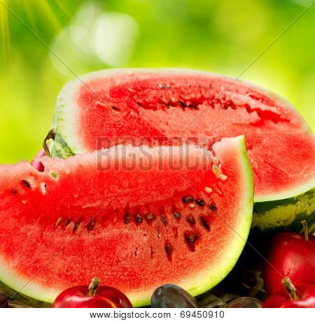 Watermelon. Juicy ripe organic watermelon slices closeup over nature green background. Autumn Fruits Still-life