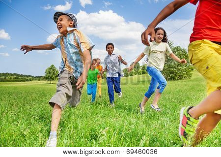 Kids in motion of running on green field