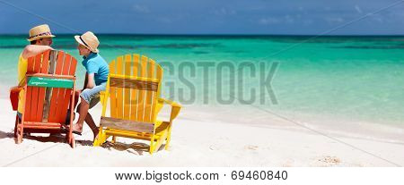 Father and son family sitting on colorful wooden chairs at tropical beach enjoying summer vacation panorama perfect for banners