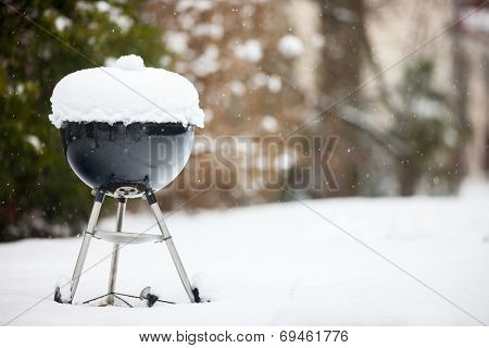 Black barbeque grill covered with snow outdoors on winter day