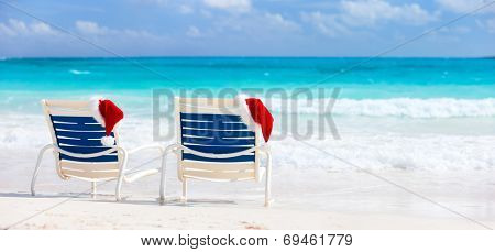 Two sunloungers with Santa hats on beautiful tropical beach with white sand and turquoise water, perfect Christmas vacation