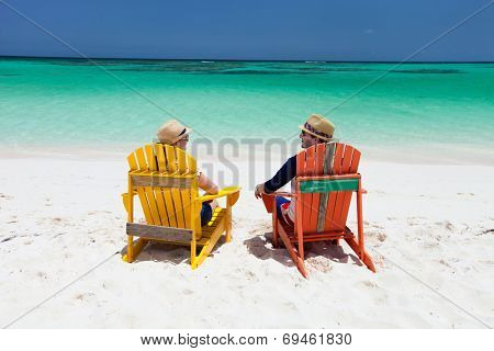 Happy couple sitting on colorful adirondack chairs at tropical beach enjoying Caribbean vacation