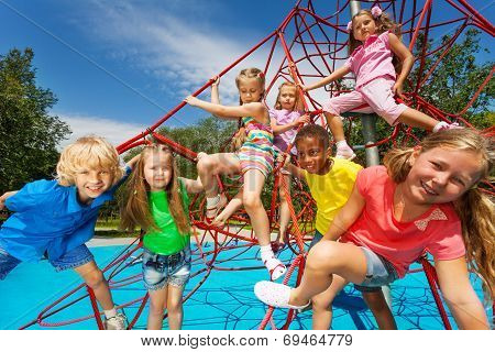 Happy group of kids on red ropes together in park