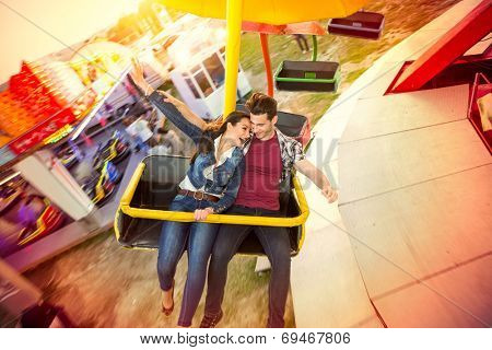 Happy couple riding on ferris wheel at amusement park
